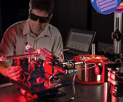Stephen Mihailov aligns an optical system for writing fiber Bragg gratings