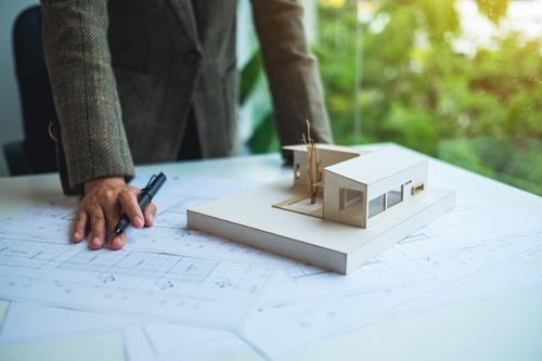 Rouleaux de dessins d'architecture avec la tablette et le modèle de maison