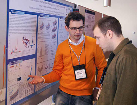 Doctoral students from Germany and Canada discuss their research at a poster session.